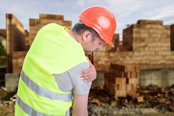 male construction worker in a hard hat grabbing his shoulder in pain