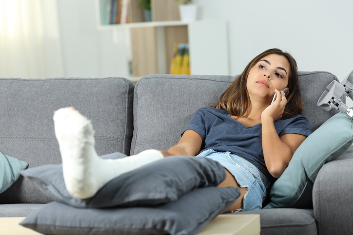 Woman with a broken foot lays on her couch and has a serious conversation on the phone