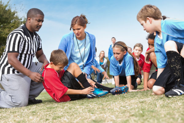 Soccer officials helping injured player during kids' game